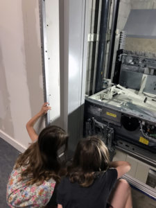 Kids looking at elevator workings